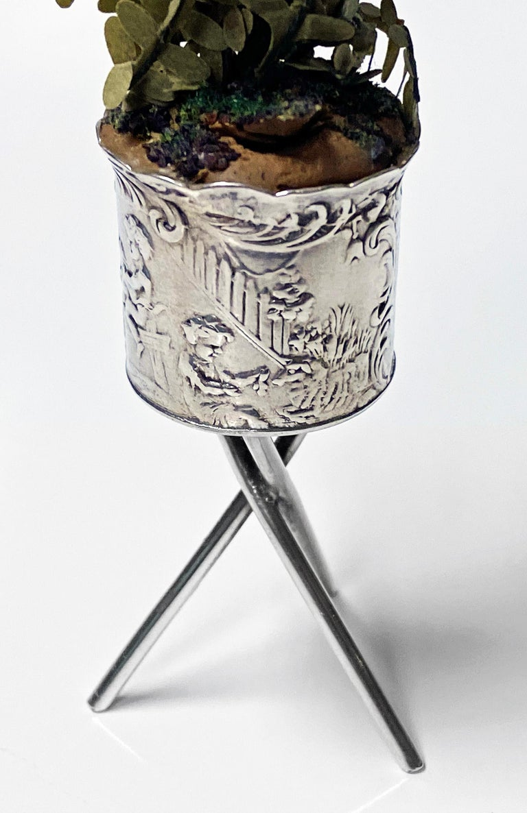 Antique silver miniature planter and stand, Germany, circa 1900. The planter with surround decoration depicting seated cherubs and figures amidst scenes with foxes, flying birds and dogs all on a crossed support stand. Pseudo German Hanau marks to