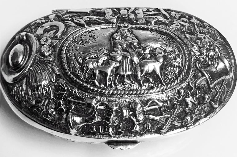 Antique Silver Neresheimer Hanau pseudo marks box of oval form, with embossed pastoral farmyard scenes to the top, the lower sides with scroll and floral decoration, interior gilt. Hanau pseudo marks and retailers stamp of Ryrie of Canada to base.