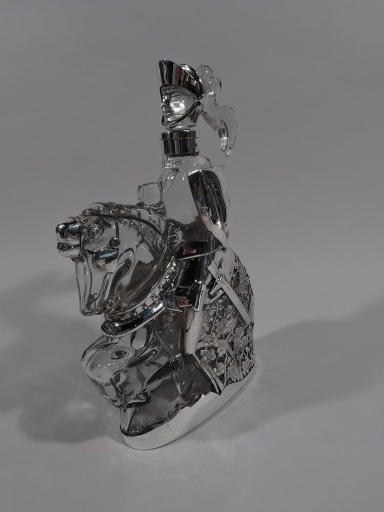Novelty clear glass and silver decanter, circa 1920. A knight errant sits astride a mighty steed, bearing shield and sword. He charges ahead, with helmet plume trailing in wind. Horse covered with dense floral armor to protect your precious tipple