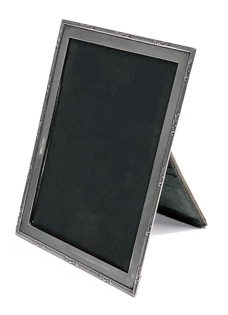 Antique silver photograph frame, Birmingham 1919, E. Mander and Son. Rectangular plain form with ribbon tie border, original velvet back. Minor wear commensurate with age. Measures: 6.00 x 4.50 inches. (Image approximately 5.50 x 4.00 inches).