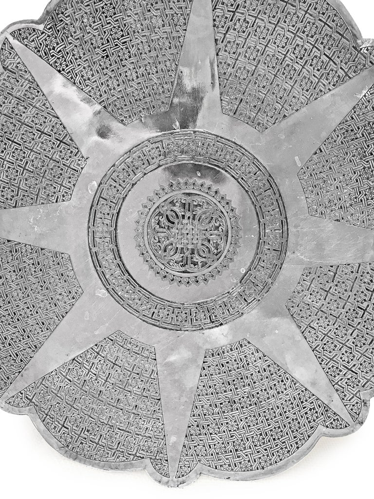 This Gorgeous silver round plate was hand-crafted in Tabriz -Iran . The unique floral and interwoven engravings are patterned around a central sun shaped design . The plate has 4 stands in the back  . You can use this plate for a lot of things even