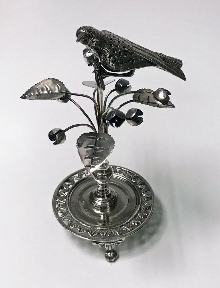 Antique silver toothpick holder, Rio de Janeiro, Brazil, circa 1850. The holder in the form of an exotic bird surmounted on bud flower foliage branches on knopped stem in turn on circular pierced foliage and wriggle work base on three turned knuckle