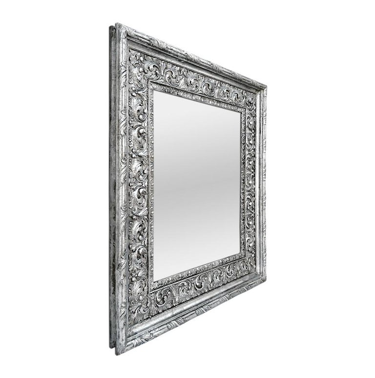 Antique silver wood mirror Baroque style, circa 1930. Decor with scrolls of foliage and fluting. Re-gilding to the patinated silvered leaf. Modern glass mirror. Antique frame width: 12 cm / 4.72 in. Antique wood back.