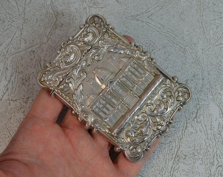 A stylish sterling silver card case or business card holder. Likely American made. Designed with floral scrolling to each side. The centre to the front boasts a 3D finish of a building. The reverse with an arrow and horn image. Hallmarks ; none,
