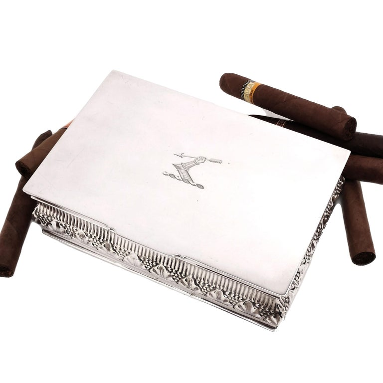 A magnificent Antique sterling Silver Cigar / Cigarette Box featuring an ornate chased design around the sides of the box and a large engraved crest in the centre. The interior base of the box is lined with cedar wood and has one movable divider.