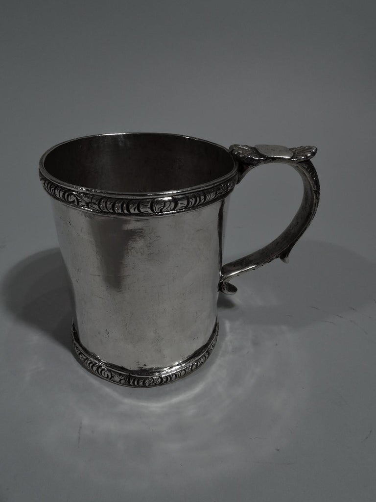 South American silver christening mug, circa 1850. Straight sides and ornamental rims with dense tooled leaves. S-scroll handle with stylized leaf-cap thumb rest and tooled flowers and scrolls. Heavy weight: 9.5 troy ounces.