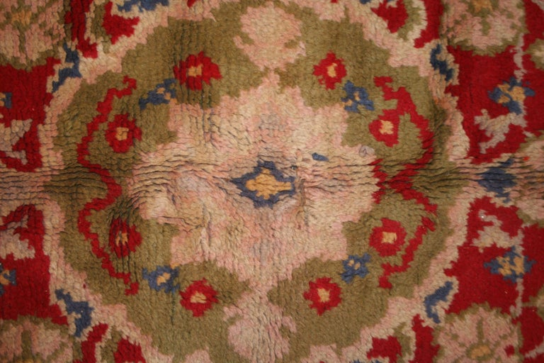A rare and unusual Art Nouveau carpet decorated by a central medallion inspired by Oriental rugs dominating over a brilliant red open field, with paisley motifs embellishing the corners and a wide border composed of stylized paisley elements on a