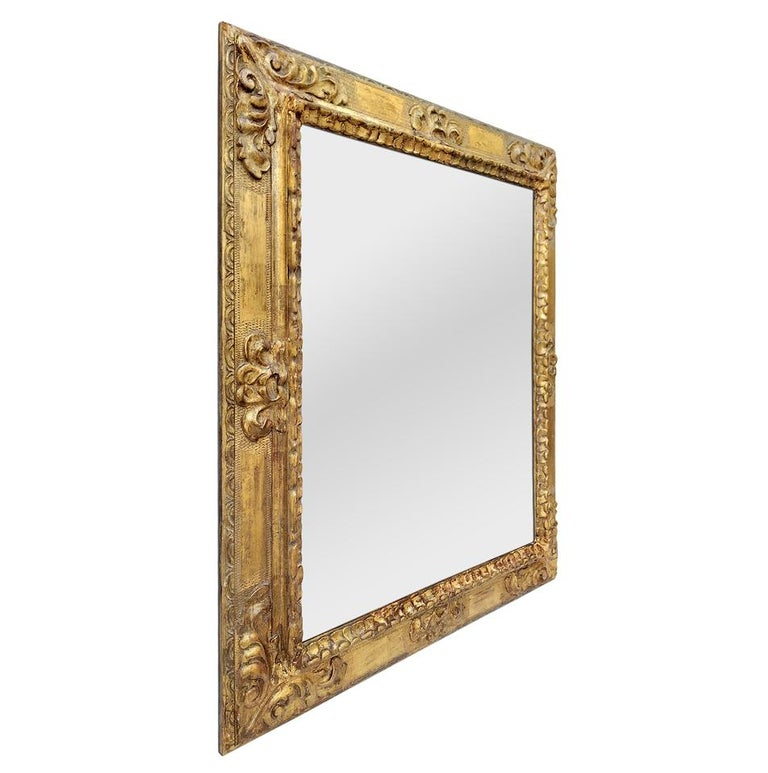 Antique Spanish style mirror frame from the 1930s. Sculpted decoration in plaster on a wooden upright. Original gilding with gold leaf. Modern glass mirror. Antique frame width 11 cm / 4.33 in.