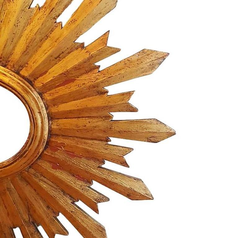 A circa 1920s Spanish gilt and carved wood sunburst mirror.  Measurements: Height 29.5