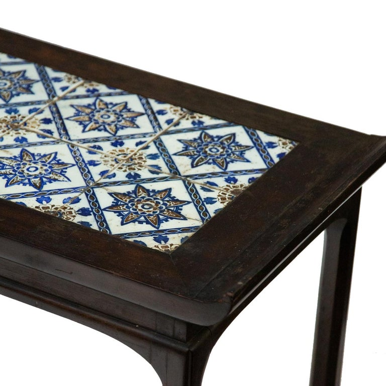 Antique Spanish tile on Chinese style table. Blue and white Spanish tiles mounted on top of Chinese style wooden table. Measures: 17.25 W x 39.5 L x 19