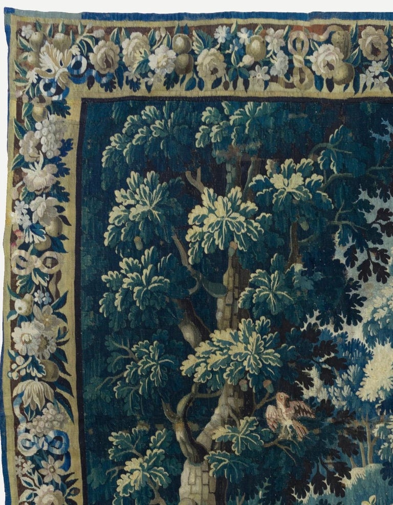 This is a gorgeous Antique Square 17th Century Flemish Verdure Landscape Tapestry with Birds depicting a beautiful and rich summer scene of a countryside with lush trees and vegetation, birds and ducks and homes in the distance. The border features