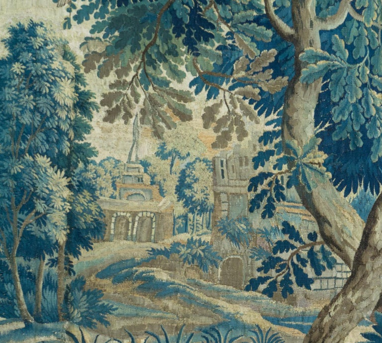 This is a gorgeous antique square 18th century flemish verdure landscape tapestry with birds depicting a beautiful and rich summer scene of a countryside with lush trees and vegetation, roosters, birds feeding their young, and homes in the distance.