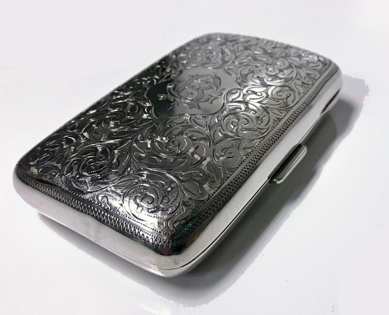 Antique Sterling Silver Cigarette Case, Birmingham 1898 JR. The case of slightly cushion rectangular form richly engraved with foliate decoration, intertwined RC or CR on one side,The interior gilded, original material band, has some wear to fabric.