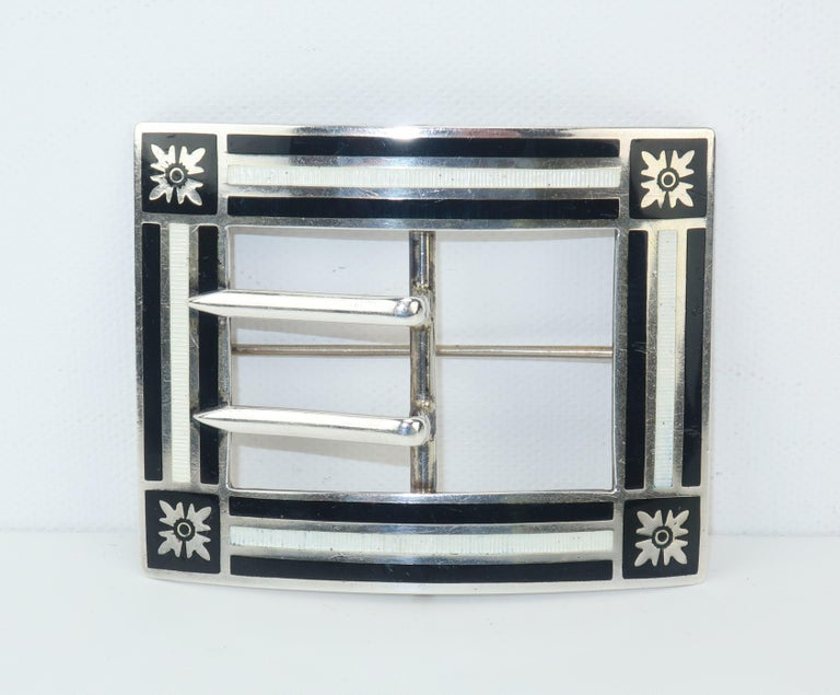 A well placed antique brooch can add stylish character to a jacket or coat and give a modern look a touch of the past.  This early 20th century sterling silver brooch has an unusually modernist style created by a black and white guilloche enamel