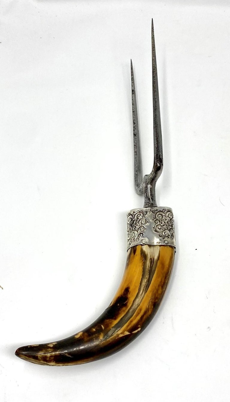 Antique sterling silver mounted boar's tusk carving fork with steel blades, circa 1900. Measures: 11
