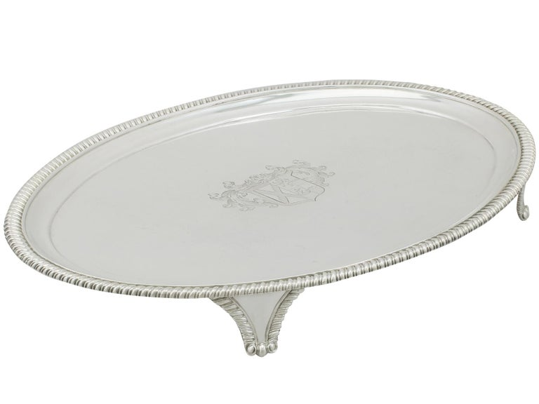 This fine antique George IV sterling silver salver has a plain oval, classic English form.   The surface of the salver is embellished with a fine and impressive contemporary bright cut engraved coat of arms with impressive scrolling leaf