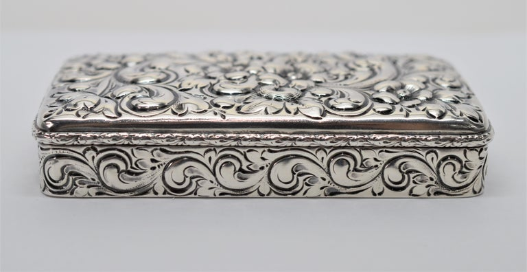 Fine Sterling Silver with American hallmarks, this antique snuff or tobacco box is beautifully created in the Nouveau style. The box measures 4 inches long x 2 inches wide and 7/8 inch deep. The hinged runs the full length of the box and with snap