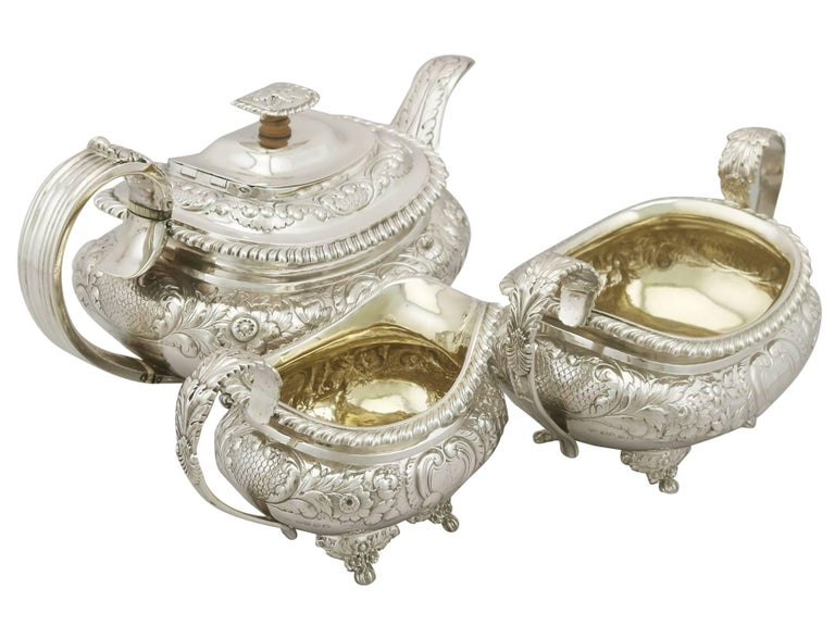 An exceptional, fine antique George IV English sterling silver three-piece tea service / set; part of our silver teaware collection.  This exceptional antique sterling silver three-piece tea service consists of a teapot, cream jug and sugar