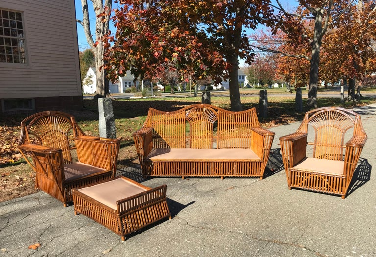 Five piece antique stick wicker set in stained natural finish. Cleaned, sealed and with new decking fabric. Generously proportioned and comfortable. Sofa measures 72