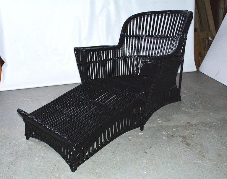 Antique stick wicker chaise lounge woven of willow newly painted in black paint. Rounded back design with flat armrest.