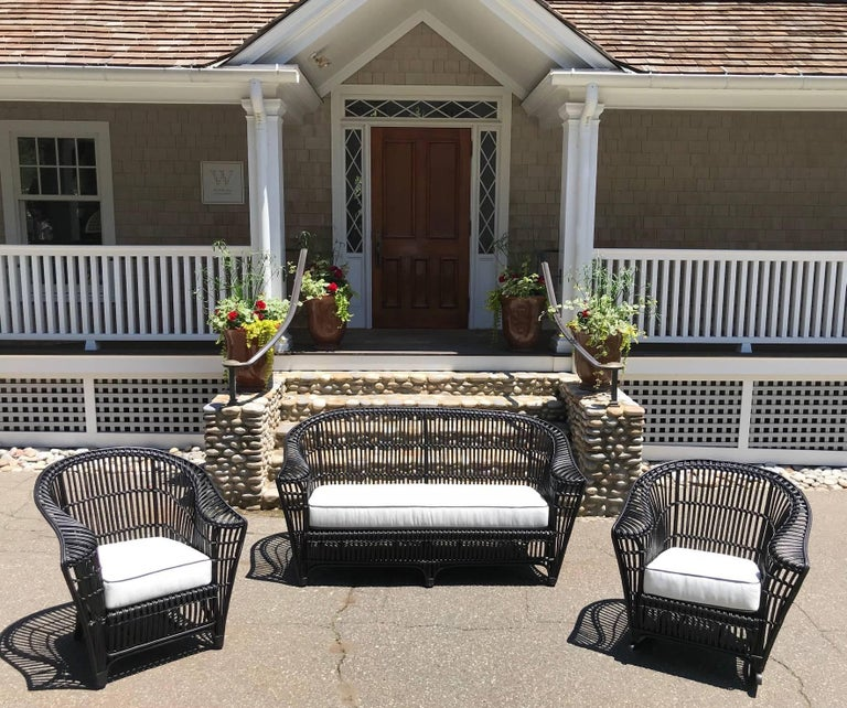 Antique stick rattan porch furniture consisting of a sofa, chair, rocker and sofa table including newly made white sunbrella cushions with black piping. Sofa measures 70
