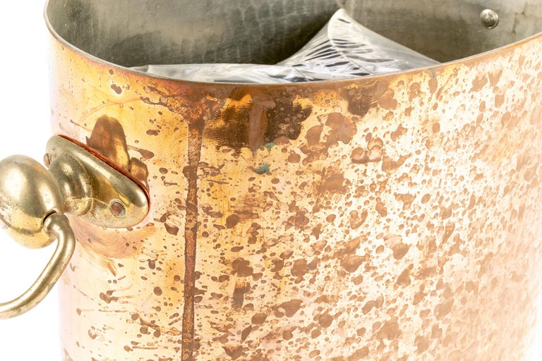 Antique hammered copper oval ice bucket with metal insert that holds two bottles, mounted with brass ring pulls. Stamped STL, Made in France.  Condition: outside needs polishing, spotted finish, slightly soiled interior.