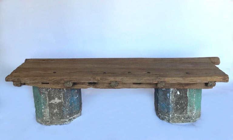 Old, weathered Japanese elm door with original iron nails, atop a pair of antique Guatemalan stone bases, make this great rustic bench. It measures 81.5 inches long, including the including the round hinge extension, otherwise overall length is 75