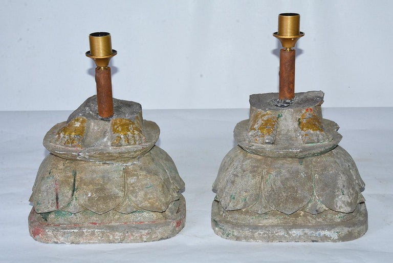 Highly unique and special, a pair of similar but not identical antique rustic organic lamps are composed of two carved stone bases made from architectural elements. Gold leafed feet that were probably fragments from Buddha statues atop lotus flower
