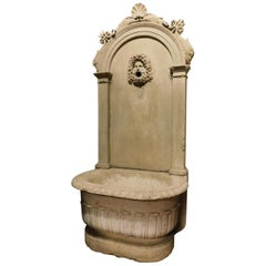 Antique stone fountain with basin and mask, carved tritons and shell, '700 Italy