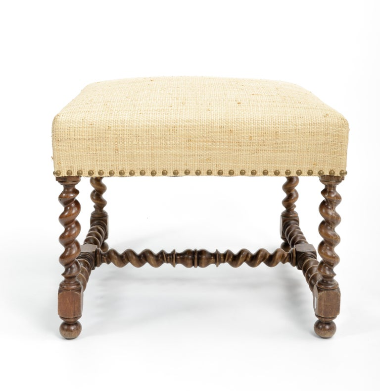 Antique ottoman/stool, Europe, 19th century.   Barley twist legs and stretchers, cream linen upholstery, and handsome nail head details.