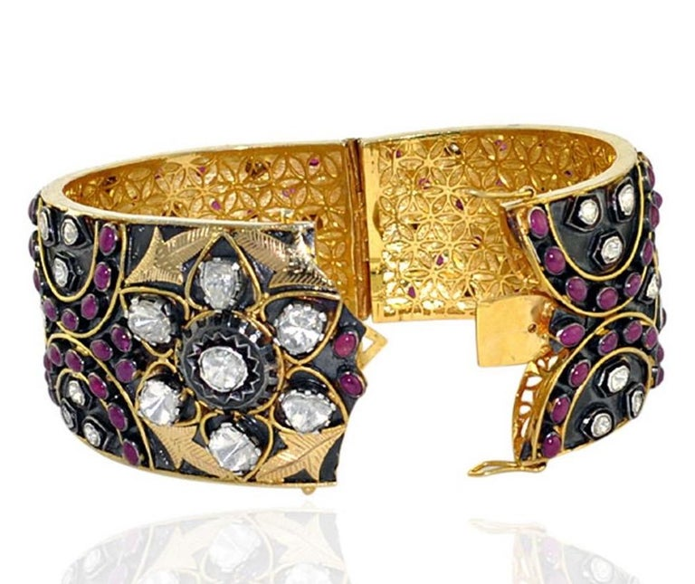 A stunning bracelet handmade in 14K gold & sterling silver with blackened finish. It is set in 24.71 carats ruby & 1.68 carats rosecut diamonds. Clasp Closure Instock  Composition Size-66X51X43 MM Total Weight-127.356 Gold Weight(Gms)-62.81 Silver