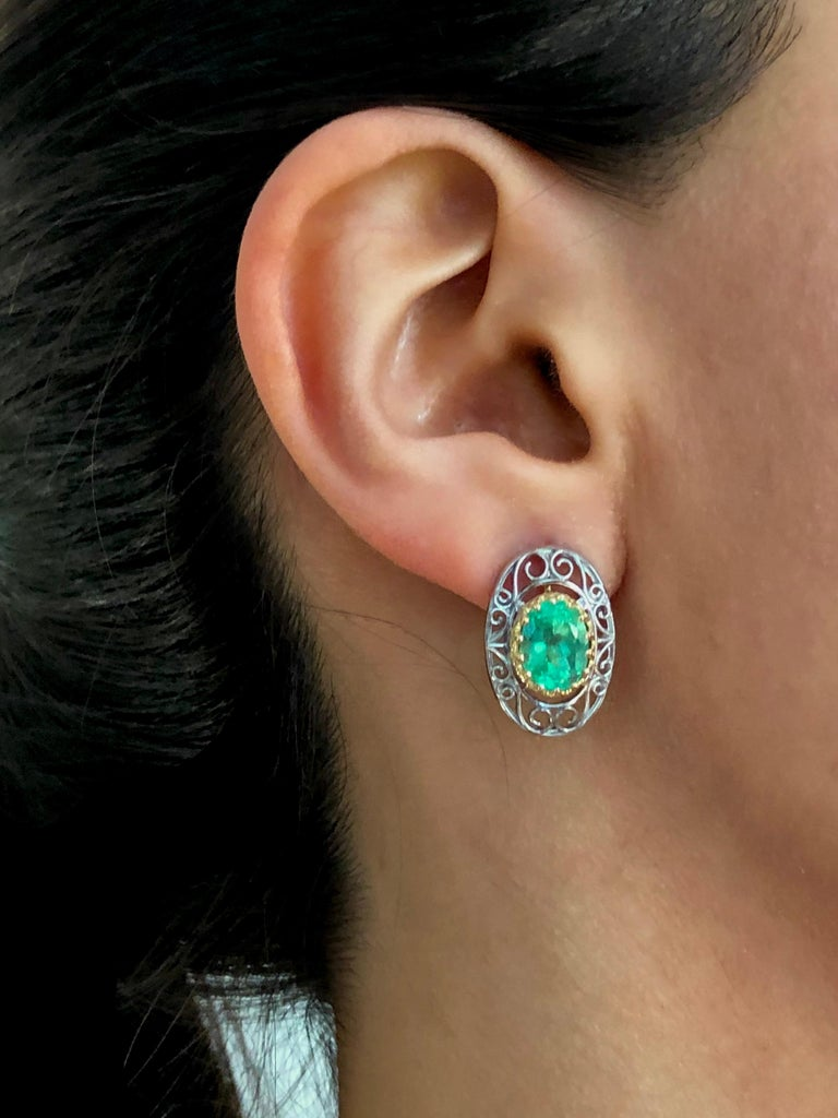 This pair of classic antique-Inspired scroll style earrings 18K yellow gold and platinum earrings is set with two natural Colombian emeralds 4.0 carats (each 2.00ct) framed by crown bezel 18K gold. Measure 20.5 x 13.5 mm Total length with ear wire