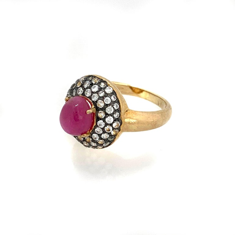 Antique-style Oval Ruby and White Topaz Bombe Cocktail Ring  This fabulous ring features a 4ct pink-ish oval cabochon-cut Mozambique ruby surrounded with 51pcs of round white topaz, handset in two-tone 18k gold vermeil and black rhodium gilded over