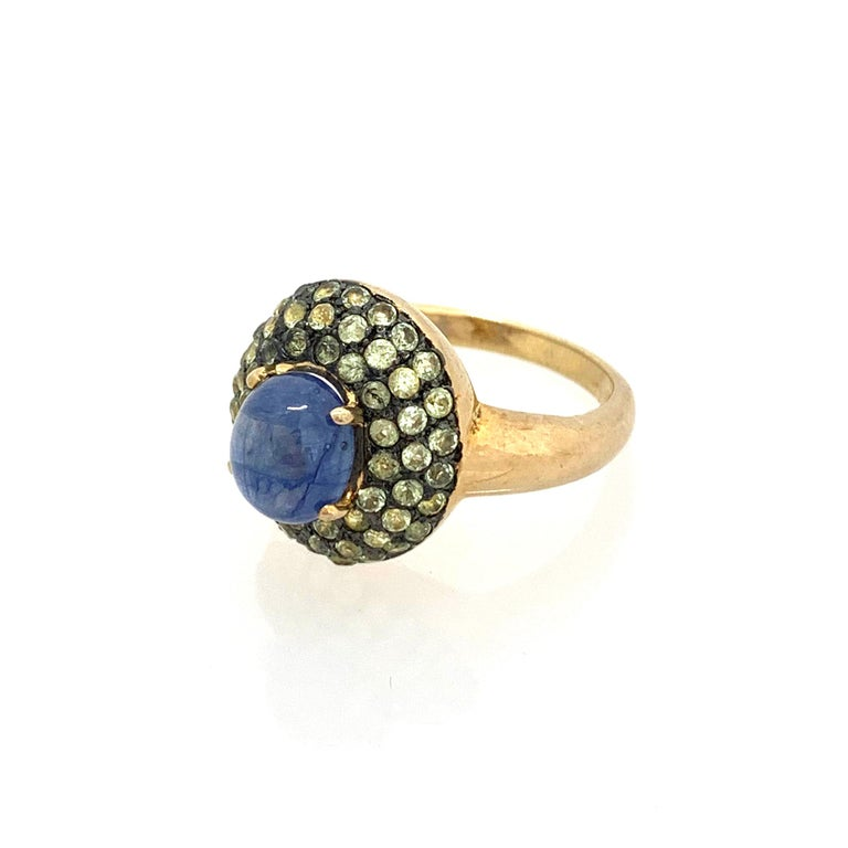 Antique-style Oval Sapphire and White Peridot Cocktail Ring  This fabulous ring features a 4ct oval cabochon-cut blue sapphire surrounded with 51pcs of round peridot, handset in two-tone 18k gold vermeil and black rhodium gilded over sterling
