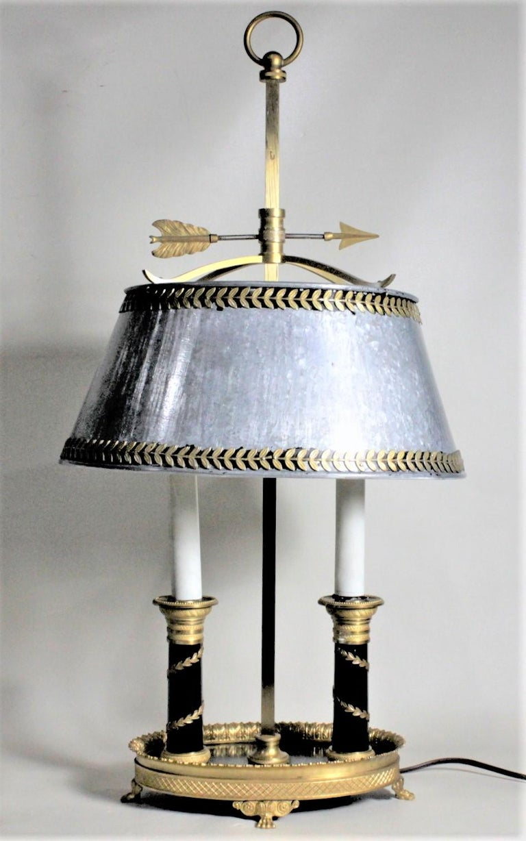 This antique styled toleware table lamp is unsigned, but presumed to have been made in France in circa 1960. The frame of the lamp and shade are cast of solid brass and the painted adjustable shade is cold-painted metal. The cast brass ring finial