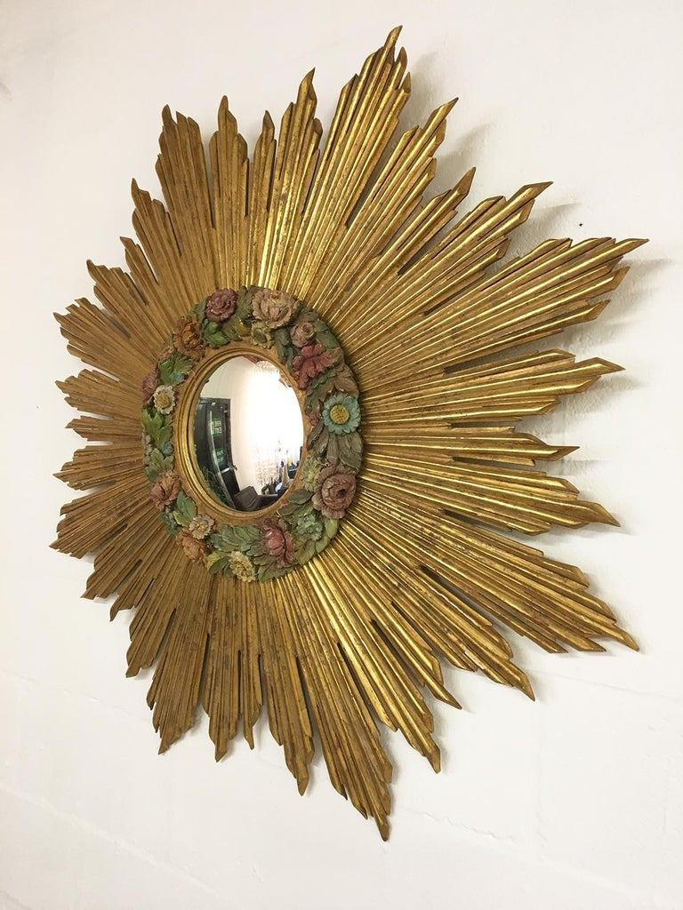 A magnificent and very large early to mid-20th century French gilded and carved wood sunburst with a convex mirror, featuring a beautiful carved and highly decorative wood polychrome Barbola wreath of flowers – which was a trend in the