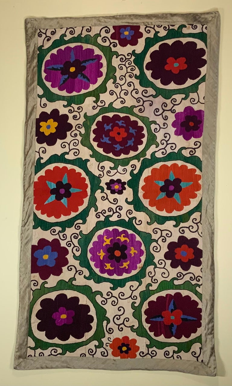 Antique Suzani textile made of hand embroidery intricate scrolling of eight large flowers motifs on a handwoven cotton background. Professionally cleaned and backed with fine textile.