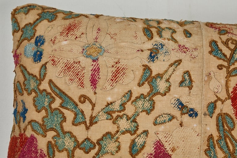 19th century Uzbek Suzani textile fragment. Silk couching and chain stitch on hand woven linen. Lovingly worn. Natural linen back, invisible zipper closure, feather and down fill.
