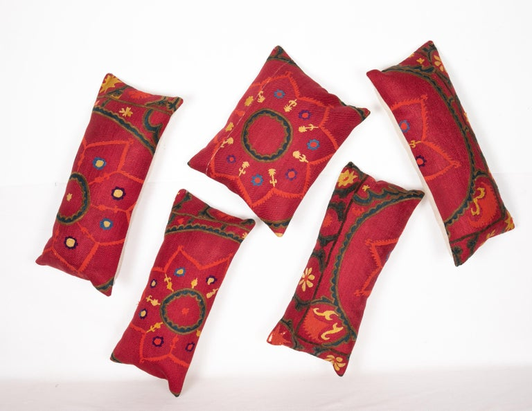 A group of 5 pillow cases fashioned from an antique Tashkent Suzani Measures: 27 x 62 cm /10.6 x 24.4 in 27 x 64 cm/10.6 x 25.1 in 29 x 63 cm/11.4 x 24.8 in 28x 58 cm/11.0 x 22.8 in 38 x 46 cm /14.9 x 18.11 in.