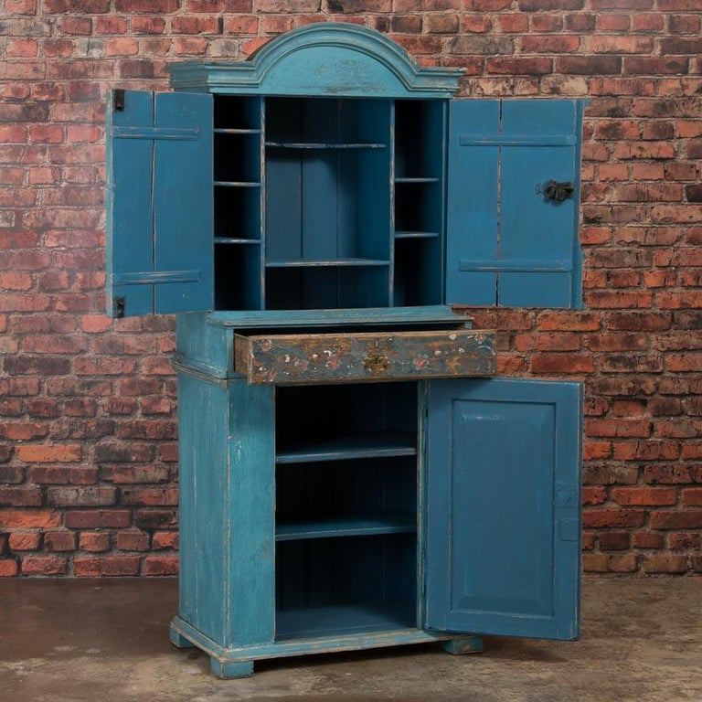 This style of cupboard with an arched molded crown, was traditionally painted in earth tones, which makes the original shade of blue on this exceptional cabinet unique. The doors and drawer are painted in a floral motif - the traditional folk art