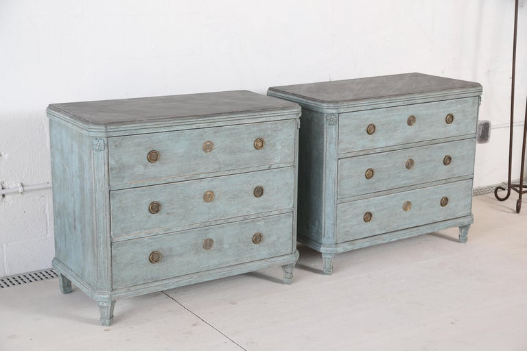 Pair of antique Swedish Gustavian style blue painted chests, each with faux painted marble tops in gray colors, three drawers with Classic Swedish brass hardware, cut corners with a rosette top and fluted,  ending with tapered fluted legs. Lovely