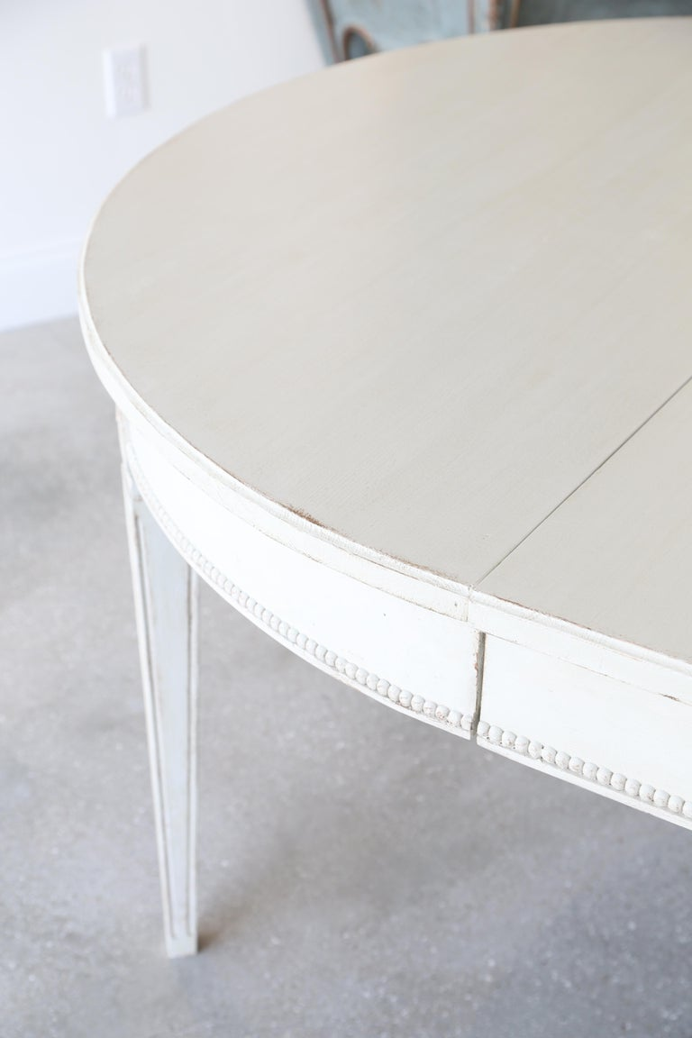 Antique Swedish Gustavian style dining table with four leaves, painted in distressed Swedish white