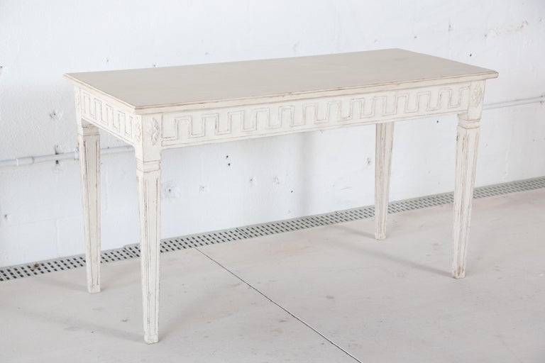 Antique Swedish Gustavian style painted console in Swedish white, apron adorned with Greek key carving and rosettes on the corners, square tapering fluted legs, simple white top, late 19th century.