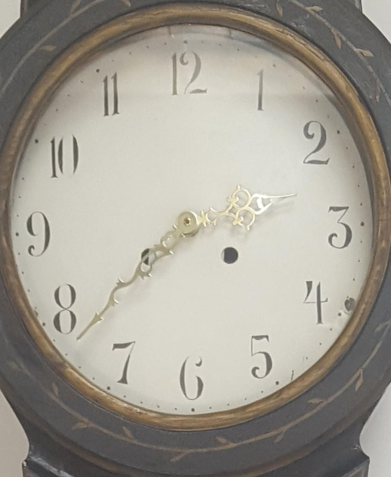 Antique Swedish mora clock from early 1800s in original black paint with hand painted gold designs and decorative face.  The clock body paint has the usual distressing/cracking and wood movement found in clocks of this age.   We will fit a