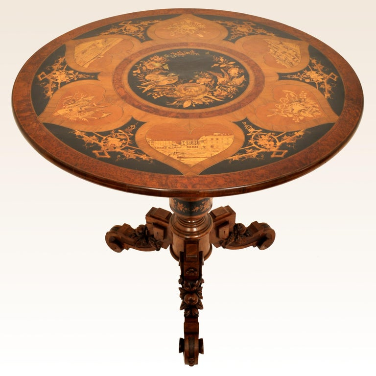 A very fine antique Swiss Black Forest tilt-top marquetry pedestal table, circa 1880.  The table having a circular top with fruit-wood and ebony inlaid panels, the central panel having a pair of nesting birds, surrounded by six panels with