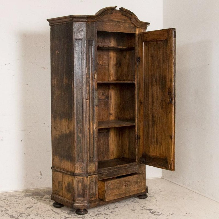 While primitive, there is a stately allure to this 7' tall single door armoire. The original paint has greatly been worn off through the distress of many years, leaving a residual amount of black and dark green paint, blended with large areas