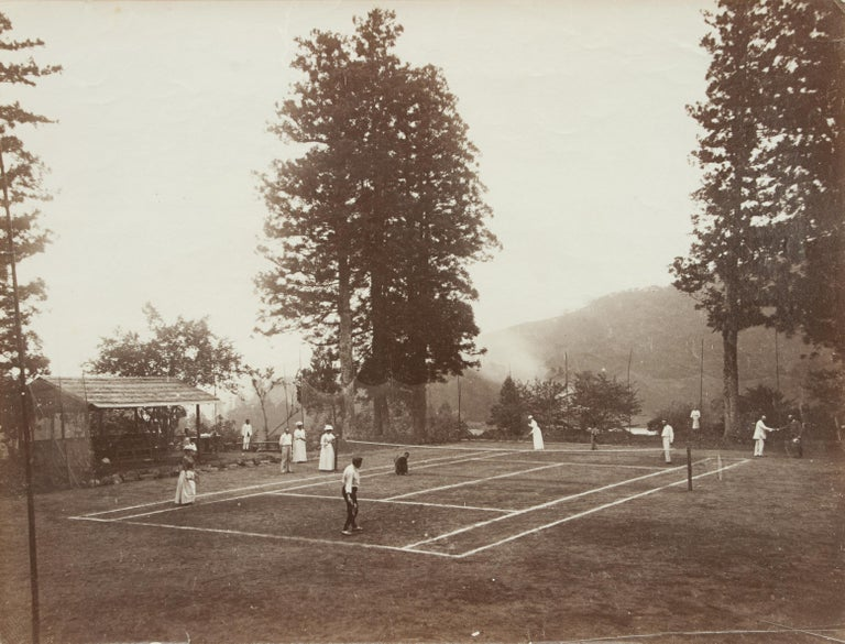 British Colonial Tennis Photograph. This black and white photograph captures the essence of British Colonial life in the late 19th century. The loose albumen print shows a game of mixed doubles in progress. There is a catch net all the way around