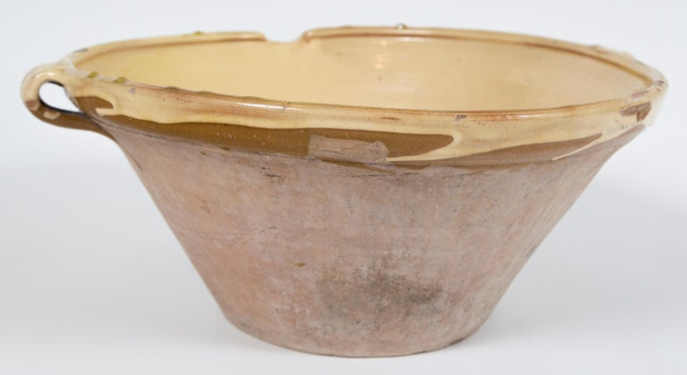 Antique terra cotta 'Tian' bowl, France, late 19th century. A large size 'Tian' with handles and spout. Pale yellow glaze on the interior and rim, unglazed exterior. Originating in the south of France, the 'Tian' was used as a mixing bowl,