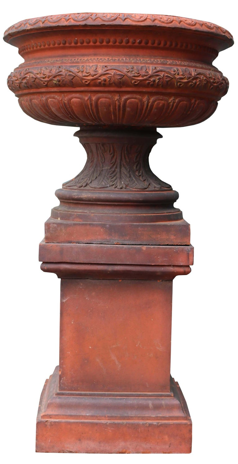 About  A large and imposing red terracotta garden urn. Reclaimed from a property in Oxfordshire.  Condition Report  The urn and plinth come in four components. There is an old hairline crack to the bowl. It is in good stable condition.