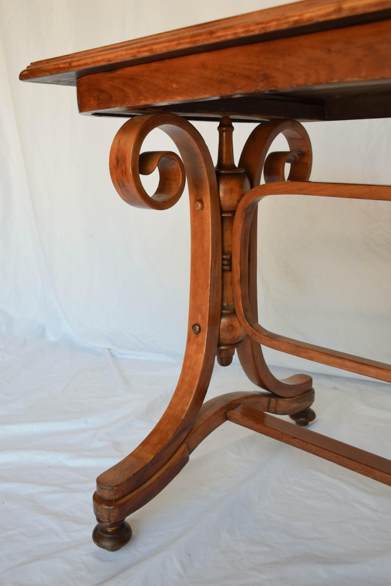 Beautiful antique Thonet Austrian bentwood table. The table, a stunning example of Thonet's artistry, has gorgeous patina. The top is two-toned with a darker wood center banded by a lighter wood with an ogee edge sitting on a stunning bentwood base.